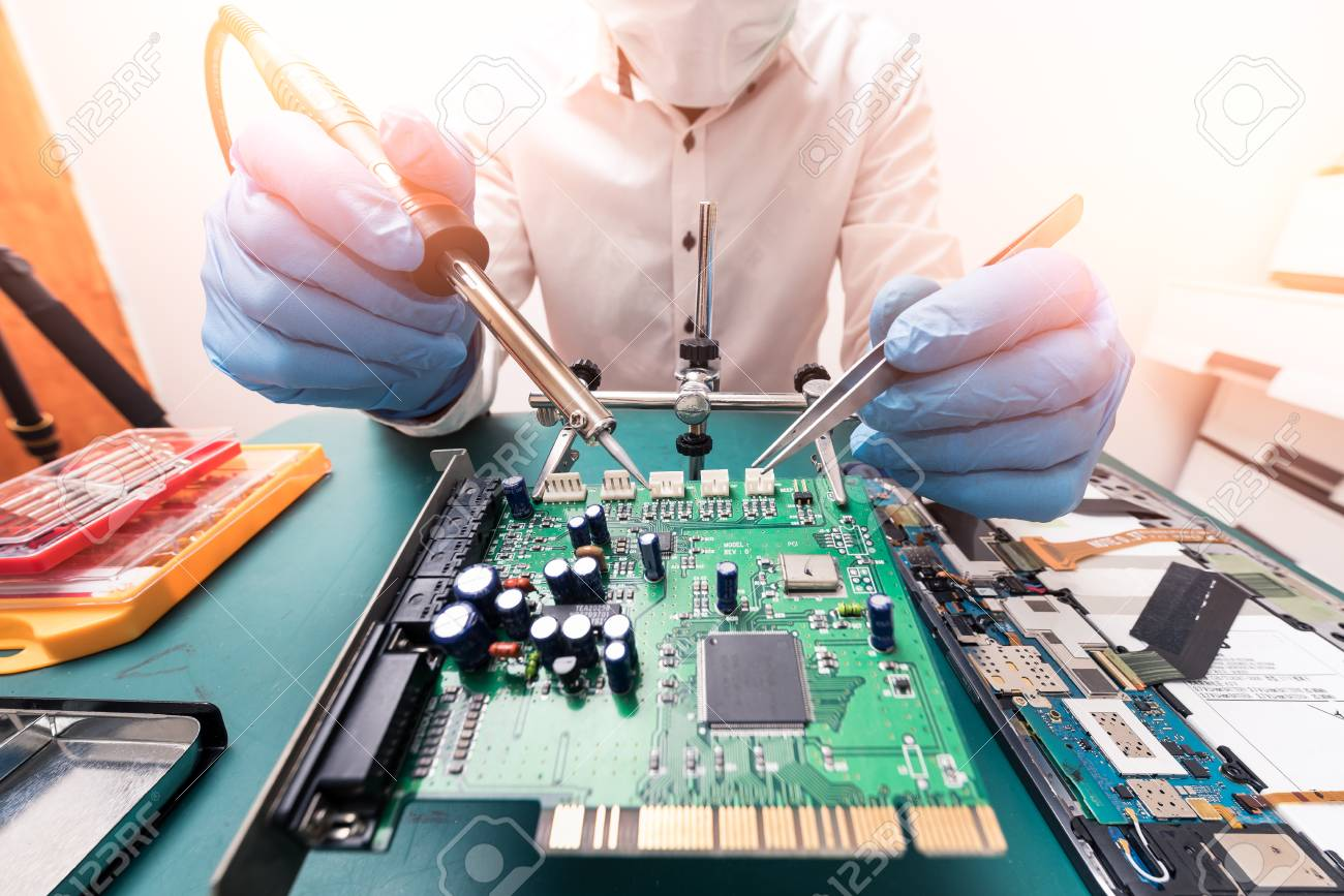 101445213-the-asian-technician-repairing-the-motherboard-by-soldering-in-the-lab-the-concept-of-computer-hardw